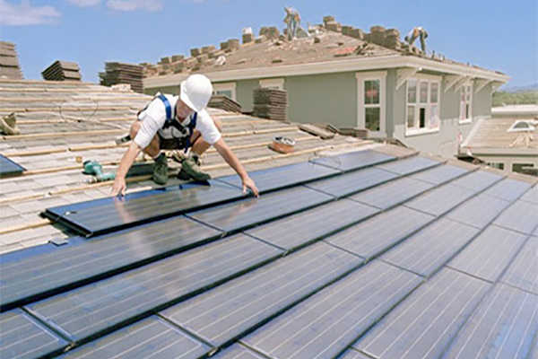 Workers installing solar panels on a residence.
