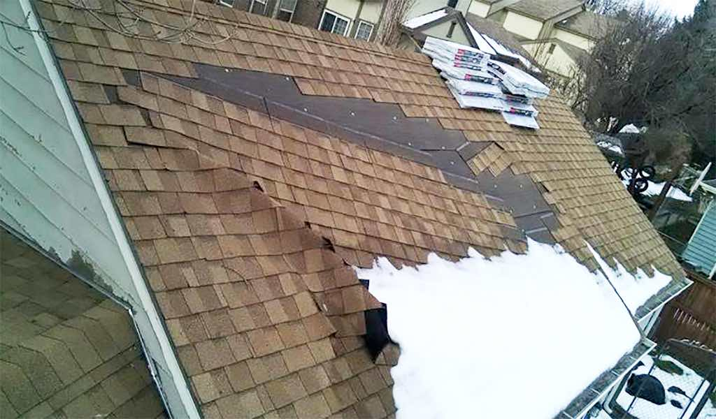 Damaged Roof With Sections Of Shingles Crumpled And Sliding Off.